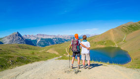 Couple of hiker on the mountain top looking at blue lake and mountain peaks. Summer adventures on the Alps. Wide angle view from a Royalty Free Stock Image