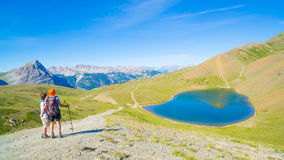 Couple of hiker on the mountain top looking at blue lake and mountain peaks. Summer adventures on the Alps. Wide angle view from a Stock Photo