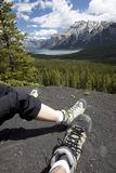 Couple of Hiker's Feet at a Mountain Overlook. A man and woman's feet are shown with hiking boots at a beautiful mountain trail scenic overlook.  In Banff Stock Image
