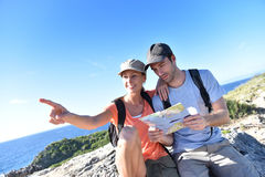 Couple of hikers admiring view on islands. Couple of hikers looking at map and scenery stock image