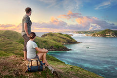 Couple hikers with backpacks enjoying sunset at mountain coast. Couple tourists with backpacks enjoying sunset at mountain coast island Lombok on top of a Stock Image