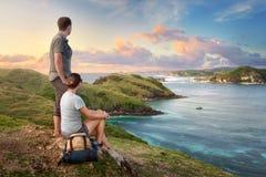 Couple hikers with backpacks enjoying sunset at mountain coast Stock Image