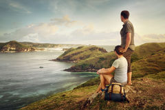 Couple hikers with backpacks enjoying sunset at mountain coast Royalty Free Stock Images