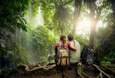 Couple hikers with backpacks enjoying view waterfall in rain for. Couple travelers with backpacks relaxing in greens jungle and enjoying view in waterfall royalty free stock images