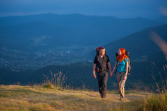 Couple hikers with backpacks holding hands, walking in the mountains. Travelers men and women with backpacks climbing up in the beautiful mountains area, holding Stock Photography