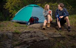 Couple of hikers with backpacks and hot tea at early morning. Tr. Avel, vacation, holidays and adventure concept. Forest Mountain landscape background Stock Photo