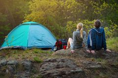 Couple of hikers with backpacks resting near the tent in the warm sunshine at sunset. Travel, vacation, holidays and adventure co. Couple of hikers with stock photography