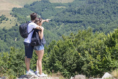 Couple of hikers with backpacks standing at viewpoint and enjoyi stock image