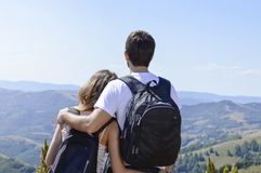 Couple of hikers with backpacks at viewpoint. Couple of hikers with backpacks standing at viewpoint and enjoying a valley view. Couple's shared activity Stock Photos