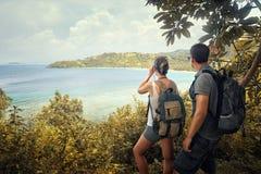 Couple hikers with backpacks watching through binoculars enjoyin Stock Image