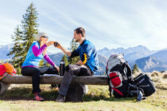 Couple hikers camping and drinking in mountains. Man and woman, hikers camping in mountains. Young couple drinking and planning trip Royalty Free Stock Photos