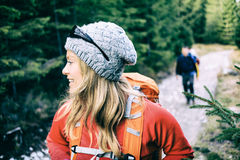 Couple hikers camping and hiking in forest. Man and women hikers walking with backpacks on trail in green forest mountains. Young couple camping and trekking on Stock Photography