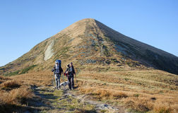 Couple hikers in the Carpathians mountains with backpacks royalty free stock image