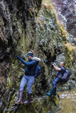 Couple of hikers climbing on safety cables in a gorge above the Royalty Free Stock Photography