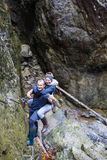 Couple of hikers climbing on safety cables in a gorge above the Royalty Free Stock Images