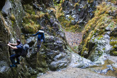 Couple of hikers climbing on safety cables in a gorge above the Stock Image