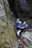 Couple of hikers climbing on safety cables in a gorge above the Stock Photography