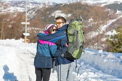 Couple of hikers exploring snowy mountain. On a sunny day Stock Photos
