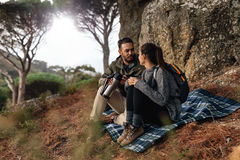 Couple of hikers having coffee break. Couple of hikers on camp having coffee break sitting on slope of mountain hill. Young men and women sitting together and Royalty Free Stock Photography