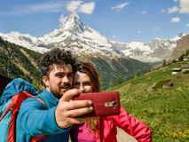 A couple hikers Hiking with backpacks walk along a beautiful mountain area. Taking a selfie. Holding the phone. The concept of active rest. Switzerland 2017 Royalty Free Stock Image