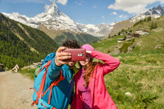 A couple hikers Hiking with backpacks walk along a beautiful mountain area. Stock Photography