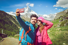 A couple hikers Hiking with backpacks walk along a beautiful mountain area. Taking a selfie. Holding the phone. The concept of active rest. Switzerland 2017 Royalty Free Stock Photo