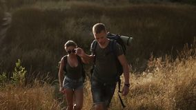 A couple hikers. Hiking with backpacks walk along hills with dre grass area while holding hands . The concept of active. Rest stock video footage