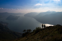 A couple of hikers look at the panorama of Lake Isea in Italy Royalty Free Stock Photography