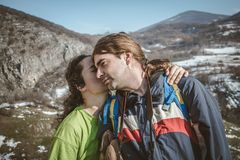 Couple of hikers on the mountain cliff. Lover women and men travel relax in the holiday enjoying on the mountain and hugging. stock photo