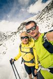Couple hikers, partnership and teamwork in winter mountains Royalty Free Stock Photo