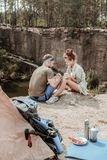 Couple of hikers relaxing while eating their lunch and drinking some hot tea. Hikers relaxing. Couple of active sport hikers relaxing while eating their lunch royalty free stock image
