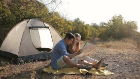 Couple of hikers resting near the tent in the warm sunshine. Reading map stock video footage