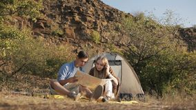 Couple of hikers resting near the tent in the warm sunshine. Reading map stock video