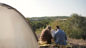 Couple of hikers resting near the tent in the warm sunshine. Reading map stock footage