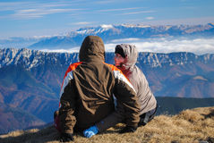 Couple of hikers sitting on the edge of the cliff Stock Photo
