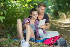 Couple hikers sitting on grass and examining map Royalty Free Stock Photos