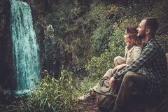 Couple hikers sitting near waterfall in deep forest. Stock Images