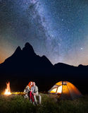 Couple hikers sitting together near campfire and glowing tent at night under stars and looking to the starry sky Royalty Free Stock Photos