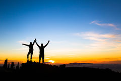 Couple hikers success concept in mountains. Couple hikers success in sunset mountains, accomplished with arms up outstretched. Man and women on rocky mountain Stock Photo