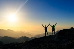 Couple hikers success and trust concept in mountains stock photography
