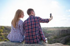Happy couple of young tourists makes selfie photo in nature. Summer trip with a loved one. Mountain selfie in summer. stock photos