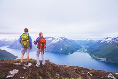 Couple of hikers on top of the mountain, group of backpackers traveling in Norway fjords. People looking at beautiful panoramic landscape stock images