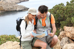 Couple of hikers visiting island with map Royalty Free Stock Photography