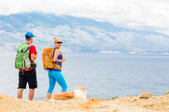 Couple hikers walking with dog at seaside and mountains. Happy couple hikers trekking with akita dog in summer mountains, camping at seaside. Young women and men Stock Photos