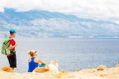 Couple hikers walking with dog at seaside and mountains Royalty Free Stock Image
