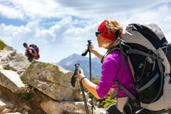 Couple hikers walking in inspirational mountains Stock Images