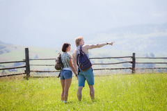 Couple hikers walking at the summer meadow. And looking around countryside view stock photo