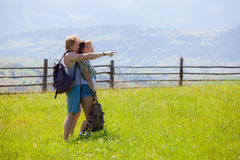 Couple hikers walking at the summer meadow. And looking around countryside view Royalty Free Stock Image