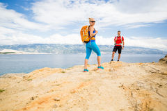 Couple hikers walking on trail at seaside Royalty Free Stock Photography