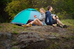 Couple hikers in the wild forest. Man and woman resting with cup. Couple hikers in the wild forest. Man and women resting with cup of tea near the tent. Travel Royalty Free Stock Image